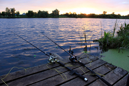 jigging: Fishing rods on the wooden bridge at sunset in autumn
