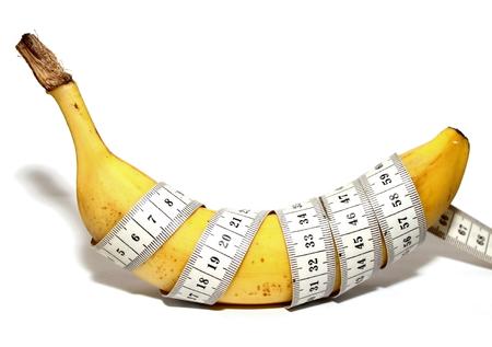 educacion sexual: Pl�tano grande y cinta de medici�n aislada en el fondo blanco, como los grandes pene del hombre, tama�o grande Foto de archivo