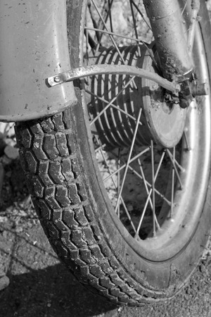 treads: Close up of motorcycle wheel  Black and white photo. Old vintage card. Stock Photo