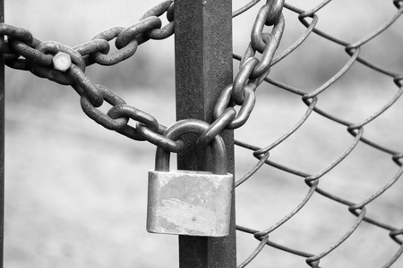 padlocked: iron padlock on iron fence with a chain-link fencing, black and white photo Stock Photo