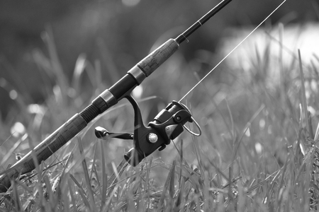 fishing rig: Fishing with rod on lake, black and white photo Stock Photo