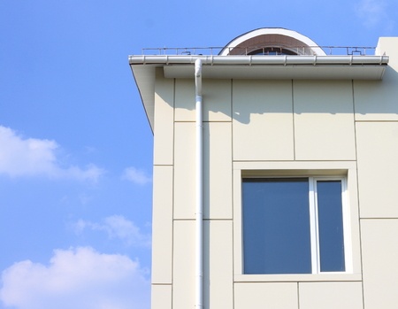 roofing system: part of a building wall with window and gutter against the blue cloudy sky Stock Photo