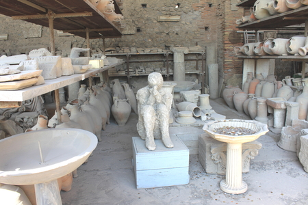 excavations: Plaster casts of victim of eruption Mount Vesuvius and ancient pottery in Pompeii - ancient Roman city in Italy. Pompeian excavations.