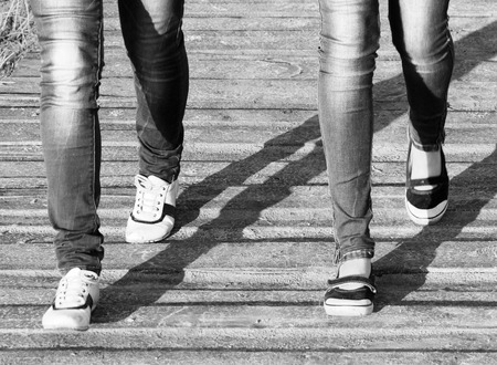 comfortable: The legs of two girls in jeans and comfortable shoes while walking  Black and white photo in a retro style