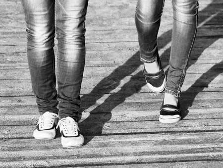 scamper: The legs of two girls in jeans and comfortable shoes while walking  Black and white photo in a retro style