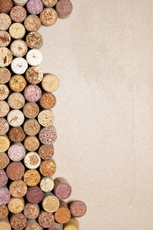 wine background: Wine corks on paper background for your text. Wall of many different wine corks with space for text. Closeup of wine corks with blurred background. Close up of cork wine on brown paper background.