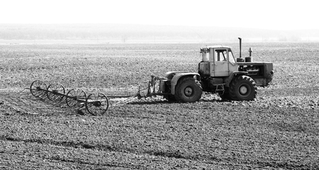 Black-and-white photo of a tractor in the field in spring