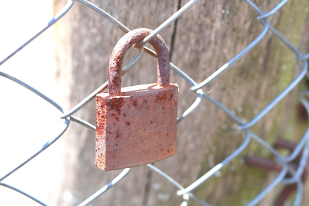Old rusty padlock on an iron fence closeup