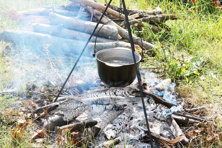 Cooking food in a pot on firewood at picnic in summer in good clear weather 版權商用圖片
