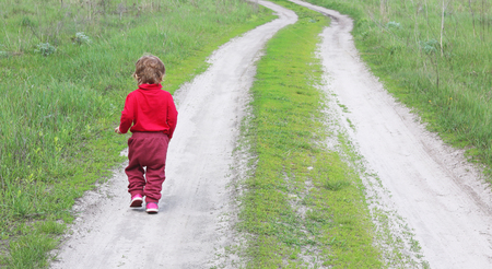 small child in red clothes from back, who runs off into distance Foto de archivo