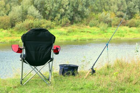 Fishing chair, rod and bait on the river bank in autumn Stock Photo