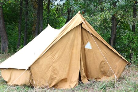Old canvas tent in tourist camp in summer on background of green trees Stock fotó