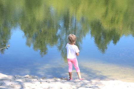 Little child fishing in summer on river