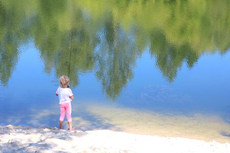 Little child fishing in summer on river on sandy shore against background of blue water and displaying green trees in river