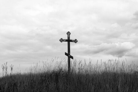 Black and white photo depicting Christian cross on hill against cloudy sky 版權商用圖片