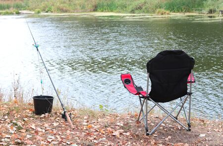 sports summer fishing with one rod and comfortable folding tourist chair on river bank