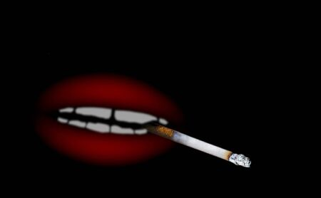 Abstract blurred image of cigarette with red shapeless mouth on black background 版權商用圖片