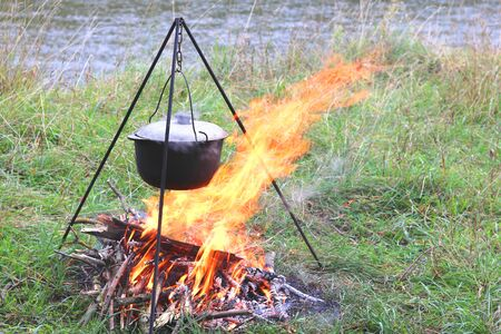 cooking delicious tasty food outdoors on fire in in summer in good weather with wood from forest