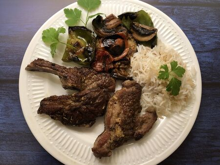 Grilled lamb chops and fresh vegetables with herbs and rice.