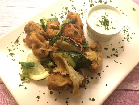 Breaded mushrooms and zucchini vegetables with delicious dip sauce tartar.