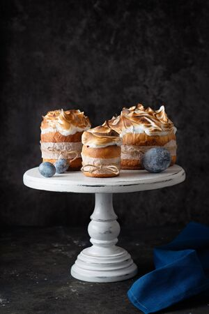 Easter cakes with colored eggs on a white cake stand with a blue napkin on a dark background. Easter card Stock Photo
