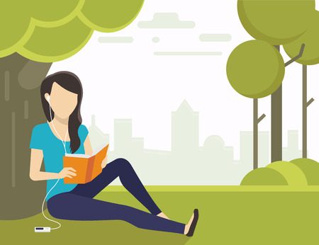 listen to music: Woman sitting on grass in the park and reading a book and listening to music