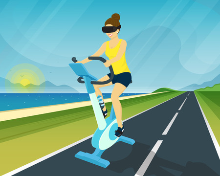 Happy woman is riding exercise bike through the scenic views using head-mounted device for virtual reality simulation
