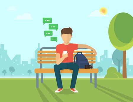 Jonge man zit in de straat en een bericht te sturen via chat naar iemand met behulp van zijn smartphone
