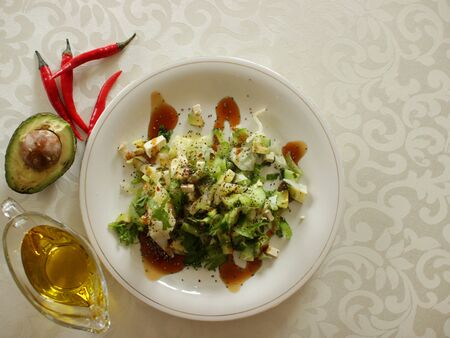 Avocado salad with cheese, celery, cucumber, lettuce and Chia seeds.Added teriyaki sauce. Salad on a white plate on a light tablecloth.Next are three red pappers, half an avocado and olive oil. Zdjęcie Seryjne