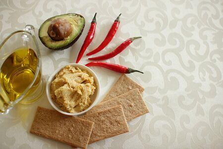 Healthy eating and food concept. Three red pappers, hummus snack from chickpea, half an avocado, crisp bread and glass gravy boat with olive oil on light background. Copy space for text. Top view.