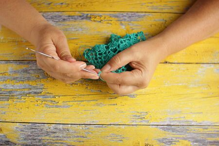 Knitting and hand crochet concept. Womens hands knit turquoise basket with a large hook from the cord. Wooden yellow background. Top view with copy space.