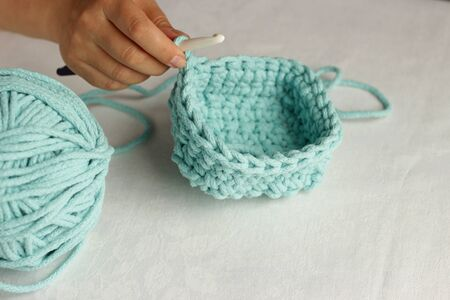 Knitting and hand crochet concept. Womens hand knit turquoise basket with a large hook from the cord. White background. Top view with copy space.