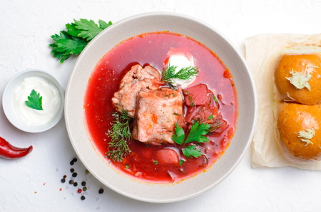 Borscht, Red Soup Made of Beetroot and Vegetables with Pork Ribs and Sour Cream Served with Garlic Rolls, Traditional Dish of Ukrainian, Russian and Polish Cuisine