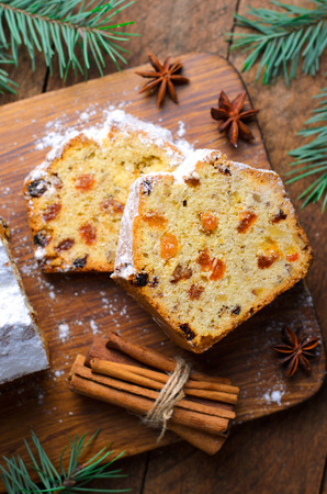 Fruit Loaf Cake Dusted with Icing Sugar, Christmas Holidays Treat, Homemade Cake with Raisins on Wooden Background