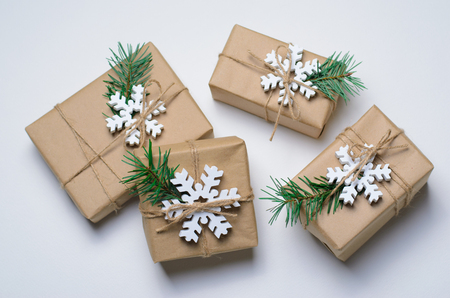 Christmas Gifts with Fir Branches and Wooden Snowflakes on White Background, Winter Holidays Concept