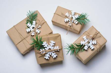 Regalos de Navidad con ramas de abeto y copos de nieve de madera sobre fondo blanco, concepto de vacaciones de invierno