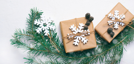Christmas Gifts with Fir Branches and Wooden Snowflakes on White Background Stock Photo