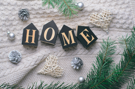 Cozy Home Winter Concept, Pine Branches and Home Letters on Beige Knitted Background, Top View