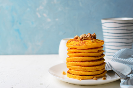 Pumpkin or Carrot Pancakes with Nuts, Stack of Homemade Pancakes on Bright Background