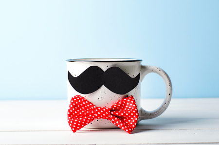 Coffee Mug with Mustache and Red Bow Tie over Blue Background, Happy Father's Day Concept