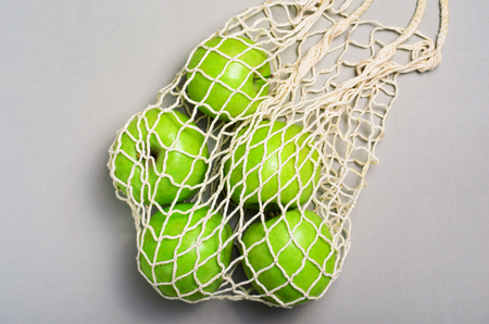 Apples in Mesh Bag, Reusable Eco Friendly Cotton Shopping Bag over Beige Background