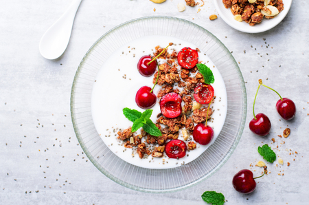 Yogurt with Cherries, Granola and Chia Seeds, Healthy Breakfast, Homemade Dessert over Bright Background