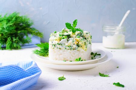 Rice Salad with Cucumbers, Eggs, Sour Cream and Herbs against Bright Background