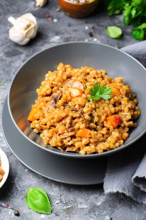 Spelt Pumpkin Mushroom Risotto on Grey Background, Tasty Vegetarian Meal
