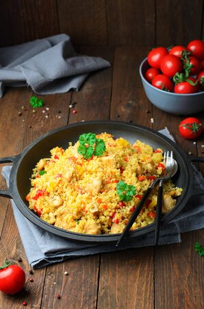 Chicken and Vegetables Bulgur in a Pan over Wooden Background, Tasty Meal