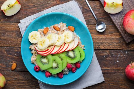 Spelt Porridge with Fruits in a Bowl over Wooden Background, Healthy Breakfast