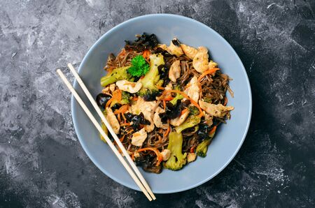 Soba Noodles with Chicken and Vegetables, Tasty Meal against Dark Background