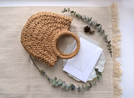 Horizontal flat lay concept. Upper view envelope with calque, cone, woven straw bag, decorative saucer and dry eucalyptus. Elegant boho upper view photo composition in soft beige color. Stock fotó