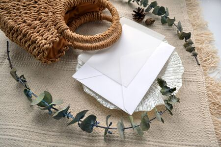 Scene envelope with calque, cone, woven straw bag, decorative saucer and dry eucalyptus. Elegant boho upper view photo composition in soft beige color. For social media, blog, stationery presentation