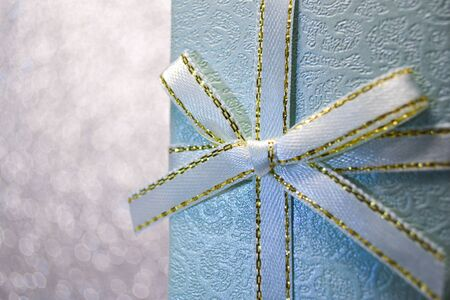 Decorative trendy blue gift box with a little turquoise and gold bow standing in a sparkle white background bokeh of twinkling party lights. Merry christmas eve winter festive macro shot concept Imagens